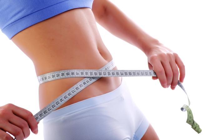 Close up of a measuring tape around slim beautiful waist.